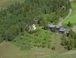 Saksumdal, stort gult hus med valmet tak. Bærbusker, skog. T