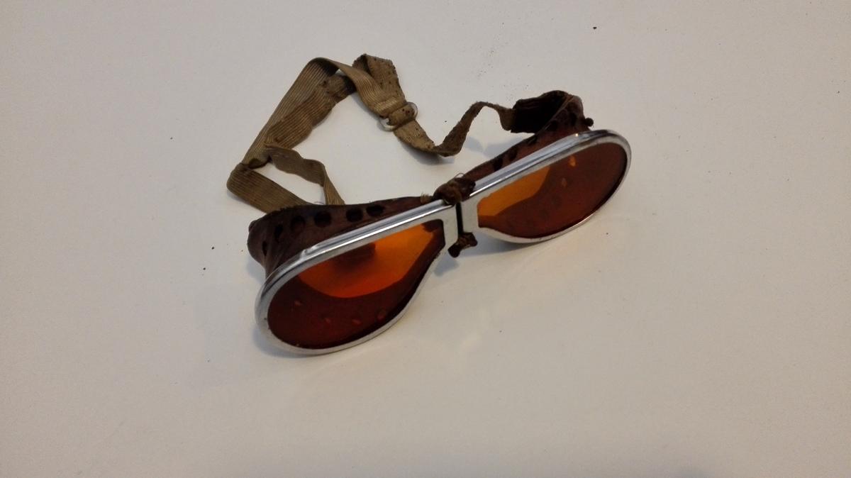 Heildekkande solbriller med oransje glas, med metallramme og skinn rundt, slik at brillene sit tett mot huda kring heile auget. Brillene vart festa med regulærbar strikk bak nakken.