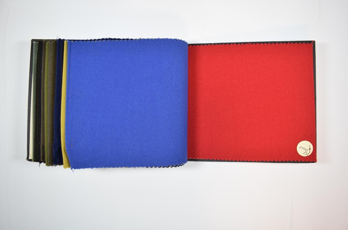 Rektangulær prøvebok med 13 stoffprøver og harde permer. Permene er laget av hard kartong og er trukket med sort tynn tekstil. Boken inneholder relativt tynne ensfargede stoff med skrå striper eller fiskebensmønster i veven. Kyperbinding/diagonalvev. Stoffene ligger brettet dobbelt i boken slik at vranga dekkes.  Stoffene er merket med en rund papirlapp, festet til stoffet med metallstifter, hvor nummer er påført for hånd.   Stoff nr.: 2500/1, 2500/2, 2500/3, 2500/11, 2500/12, 2500/13, 2500/26, 2500/27, 2500/28, 2500/29, 2500/30, 2500/31, 2500/32.