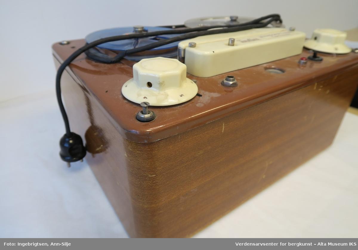 En rektangulær boks i tre med metallplate. På metallplaten er det montert to hjul med lydbånd, og under disse er det en hvit båndopptaker/avspiller.