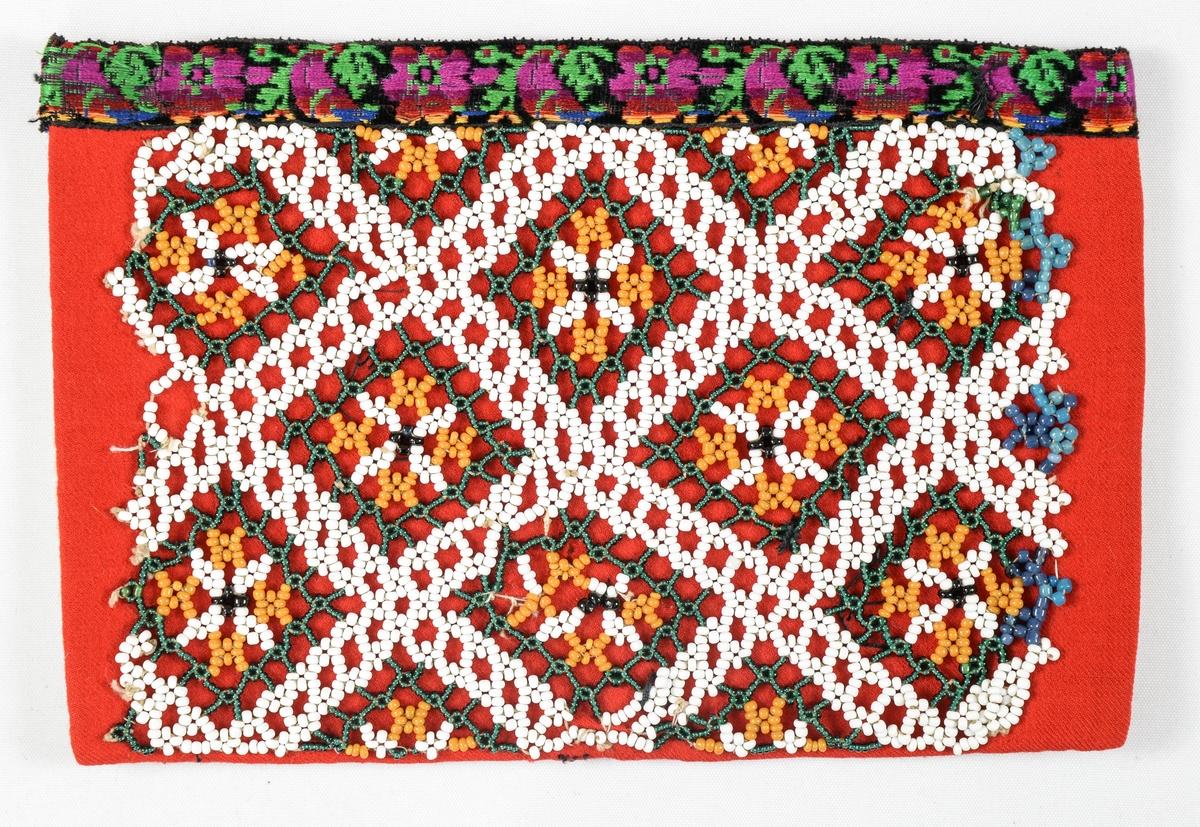 Bringeduk i raudt kypertvove ulltøy dekorert med perlebroderi i ulike farger. Kanta øverst med eit mønstra band i grønt, rosa, raudt og svart. Fóra med ubleikt bomull.