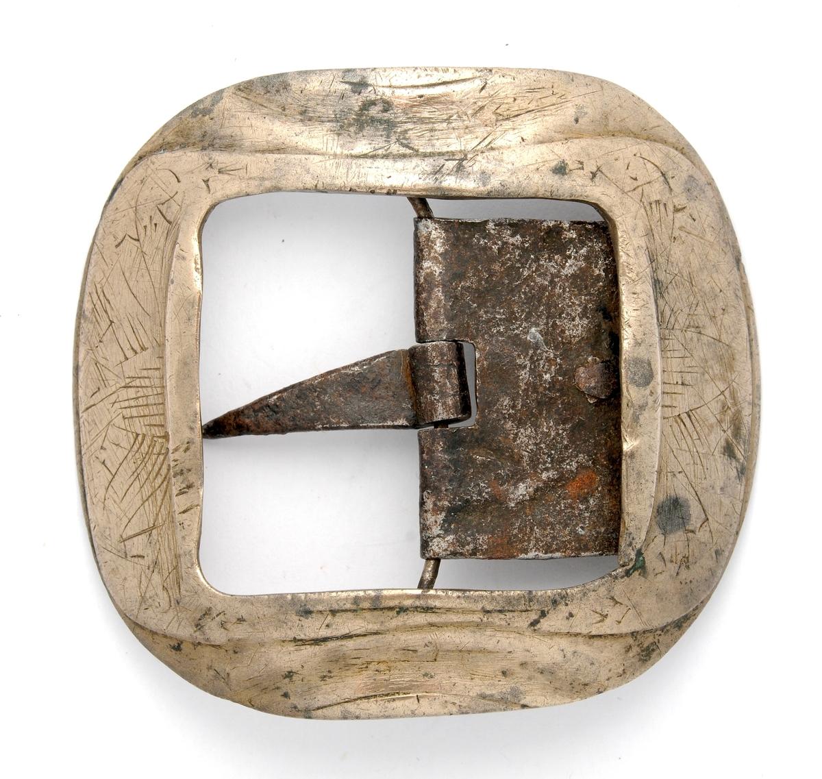 Spenne, A og B,  i støypt messing, firkanta med runde hjørner. A manglar stolpe, tann og kalv, på B er dette smidd i jern.