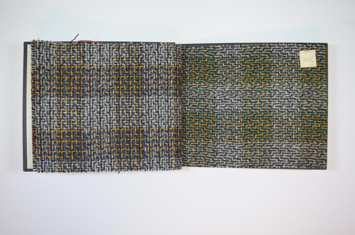 Rektangulær prøvebok med harde permer og tre stoffprøver. Permene er laget av hard kartong og er trukket med sort tynn tekstil. Boken inneholder middels tykke ullstoff med ruter og strekmønster. Stoffene er merket med en firkantet papirlapp, festet til stoffet med metallstifter, hvor nummer er påført for hånd.   Stoff nr. 6014/1, 6014/2, 6014/3.