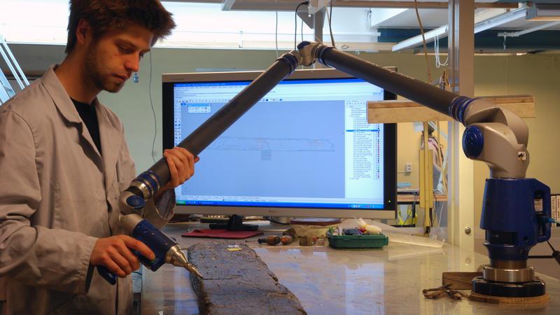 Arkeologene 3D-dokumenterer hver enkelt båtdel. Arkeolog dokumenterer hudbord med FARO-arm.