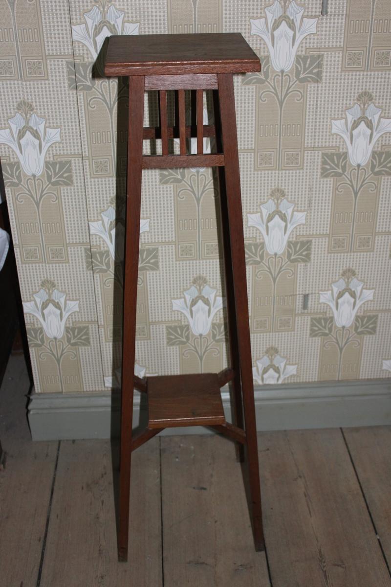 Piedestal i enkel modell, tillverkad i ek. Avsmalnande uppåt. Två fyrkantiga skivor för blomkrukor, en upptill och en nedåt till på benställningen. Den nedre hålls fast av korslagda pinnar. Under den övre skivan finns ett ramverk med lodräta pinnar.