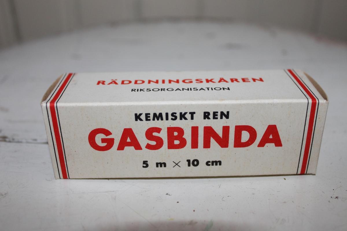 Gasbinda med förpackning i kartong. Tillhör Räddningskårens förbandslåda. På kanterna sitter Räddningskårens logga.