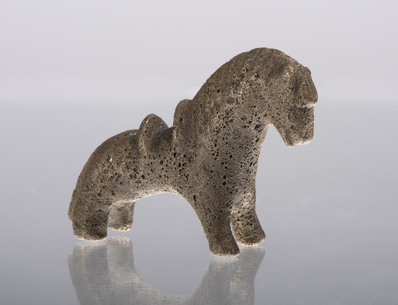 Et nydelig lite vektlodd formet som en bronsehest med sal på ryggen.