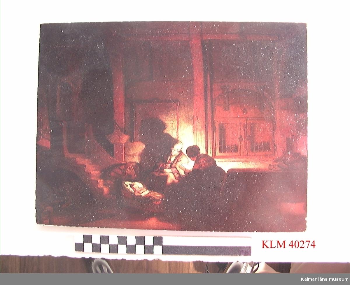 """KLM 40274 Tavla, reproduktion. 1600-talsinteriör, familj med litet barn i vagga. På  baksidan står det """"Badhotellet, Amsterdam 1970"""" med blå kulspetspenna samt tryckt """"REMBRANDT VAN RIJN (1606-1669) /DE HEILIGE FAMILIE""""."""