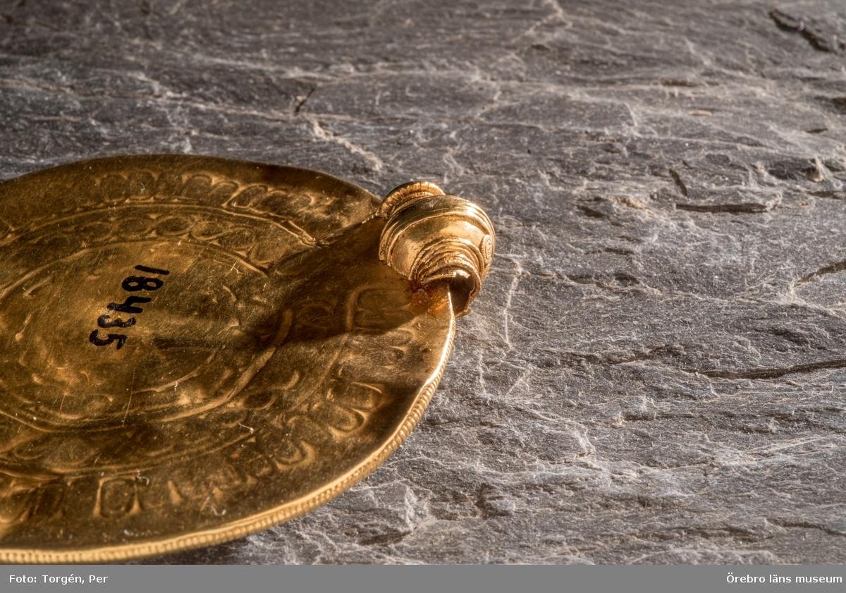 Brakteat från järnåldern. Av guld.  Rund, upptill med profilerad hylsa för band eller kedja. Hylsan jämte en från densamma nedgående flik med filigrandekor. Två plattor av guldbleck, den främre med pressad dekor: koncentriska spiral-, strecktecknade och andra band; i centrum figur: fyrfotadjur samt över detta ett stort människoliknande huvud. Fyndort Hässleberg, Viby sn.  Mått: Diameter: 71 mm. Höjd med fäste: 75 mm.Från Närke, Viby socken, Hässleberg. Köpt av lantbrukaren Algot Gustafsson, Hässleberg, som fann den på Halla äng. Publ: I Meddelanden från Föreningen Örebro läns museum XIII, 1941, s.7, Lars-Göran Kinström: Vibybrakteaten och andra fornfynd av ädelmetall i Närke.