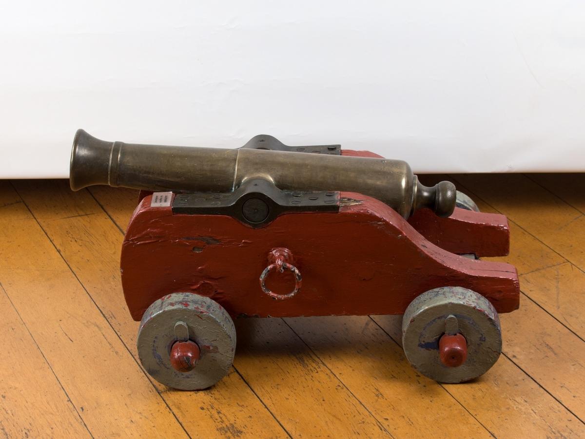 Saluttkanonen i messing. Lavett og hjul av tre. Treverket er malt rødt og grått.