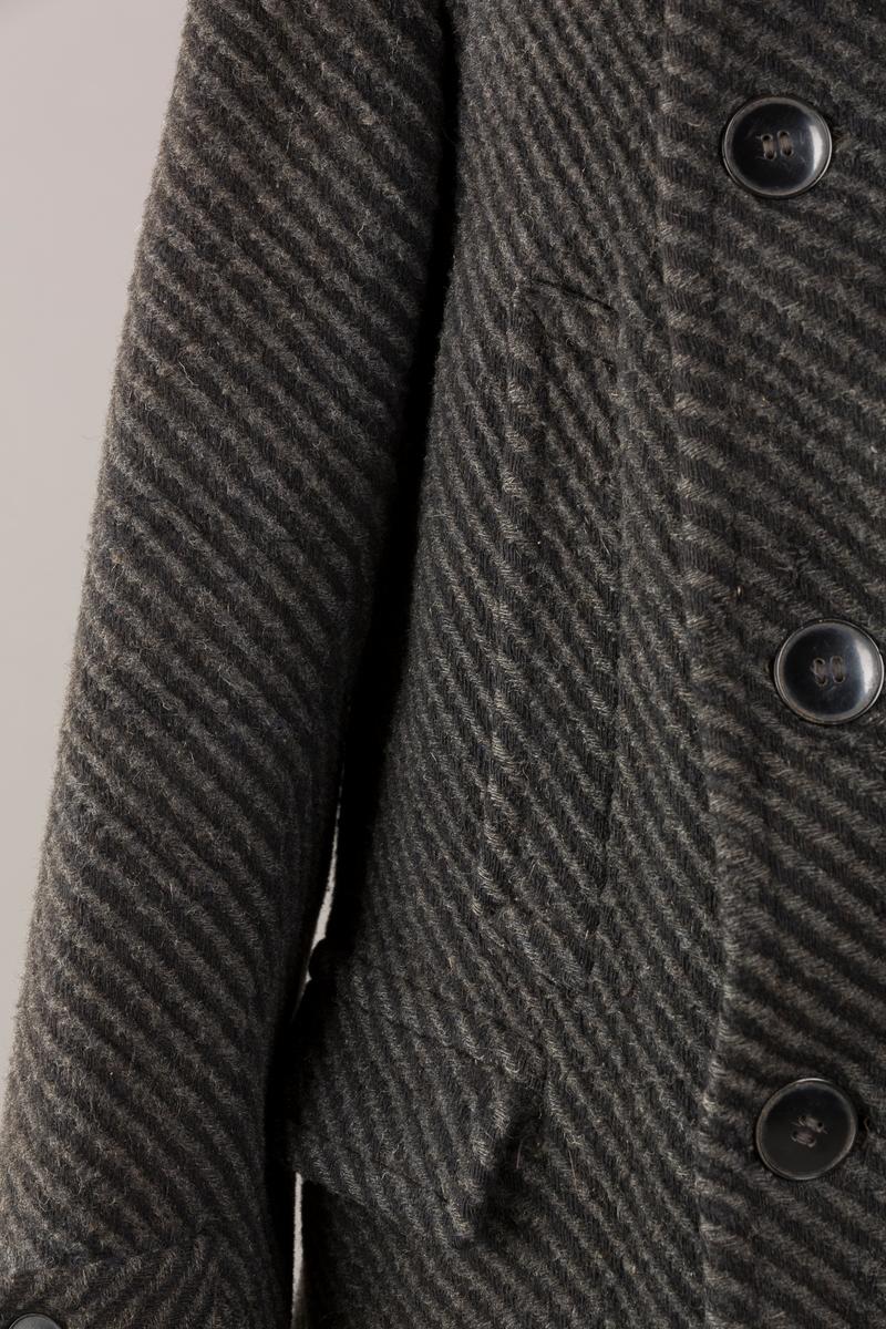 Plagget er svakt utskrådd med høy krage. Spensel lukker kragen. Frakken er dobbeltspent med 2 x 4 knapper og knapphull på begge sider, men totalt er det 23 knapper Spensel med knapp nederst på ermene. To lommer med lommeklaff. To stikklommer på magen. Spensel i ryggen. To innelommer. Foret med ull og silke (i ermene). Foret er rutemønstret. Vevd i to farger, grå og sort. Hempe i krage.