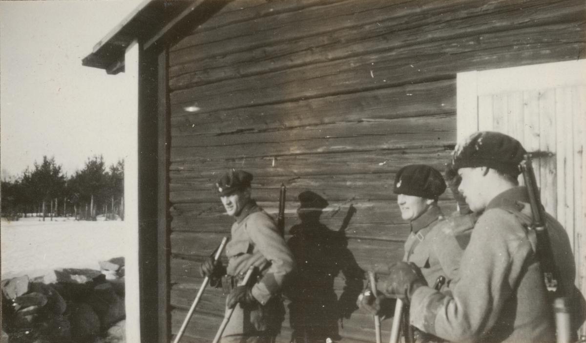 Tre soldater från Göta livgardes stridsvagnsbataljon framför en byggnad.