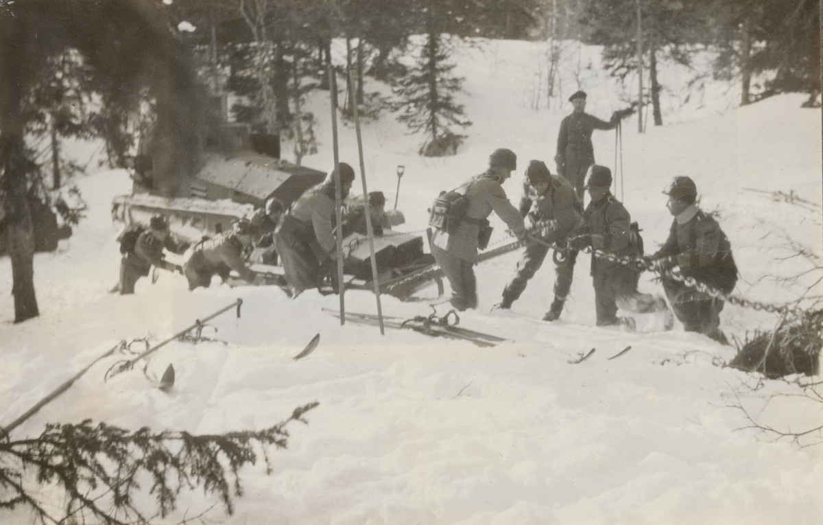 Stridsvagn m/1921 (eller m/1921-1929) fast i snö. Elever från stridsvagnskursen vid Göta livgardes stridsvagnsbataljon fäster dragkedjor för att få loss vagnen.