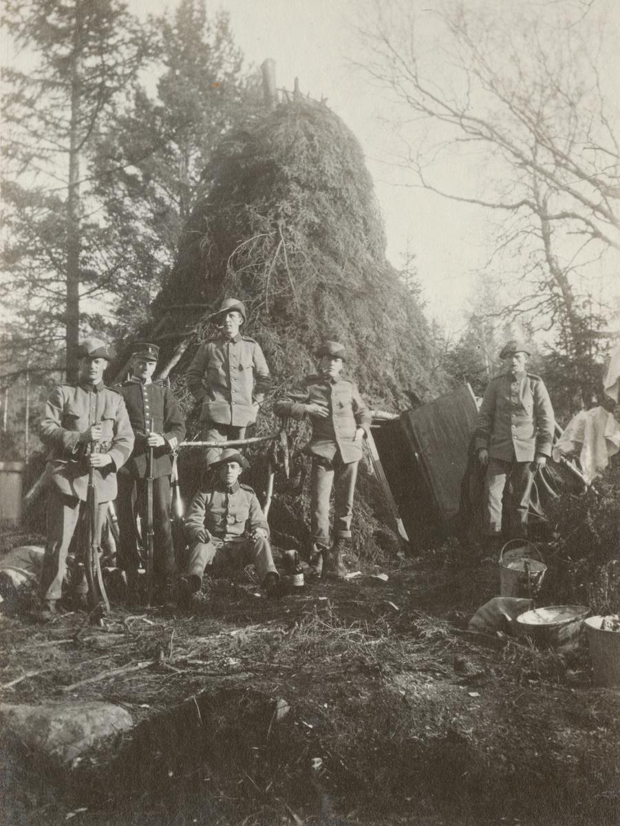 Gruppfoto av soldater från Göta livgarde I 2 framför en bivack.