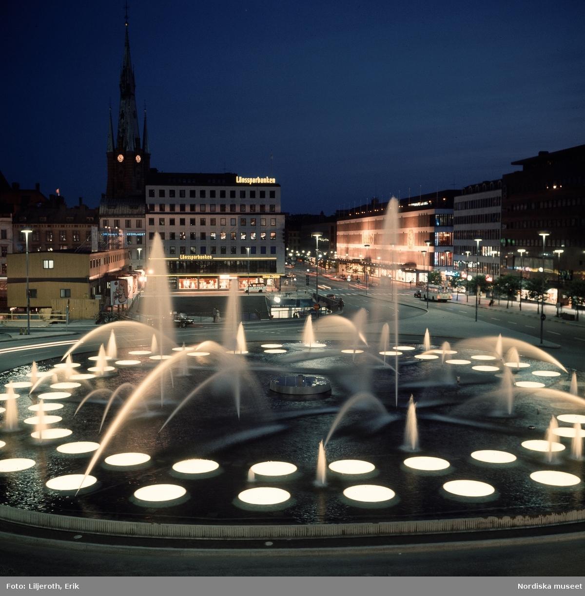Sergels torg, Stockholm, kväll. Utsikt mot entrén till T-centralen, Åhlénshuset och Klara kyrka.
