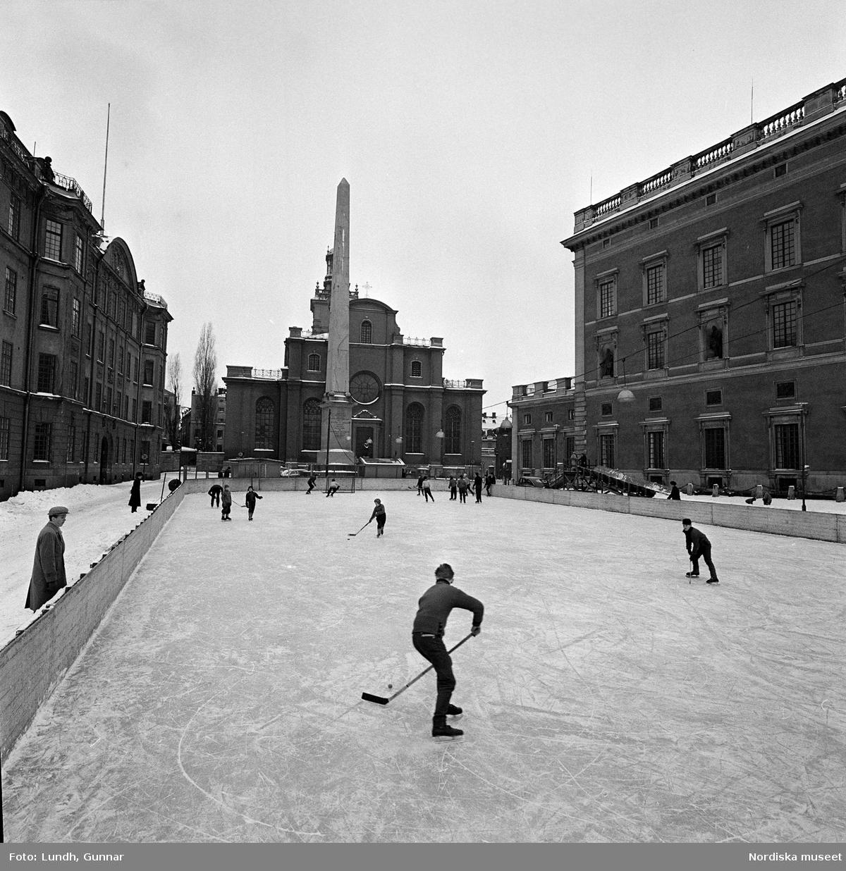 Ishockeyspelare och skridskoåkare i rink utanför kungliga slottet i Stockholm. Slottsbacken, obelisken.