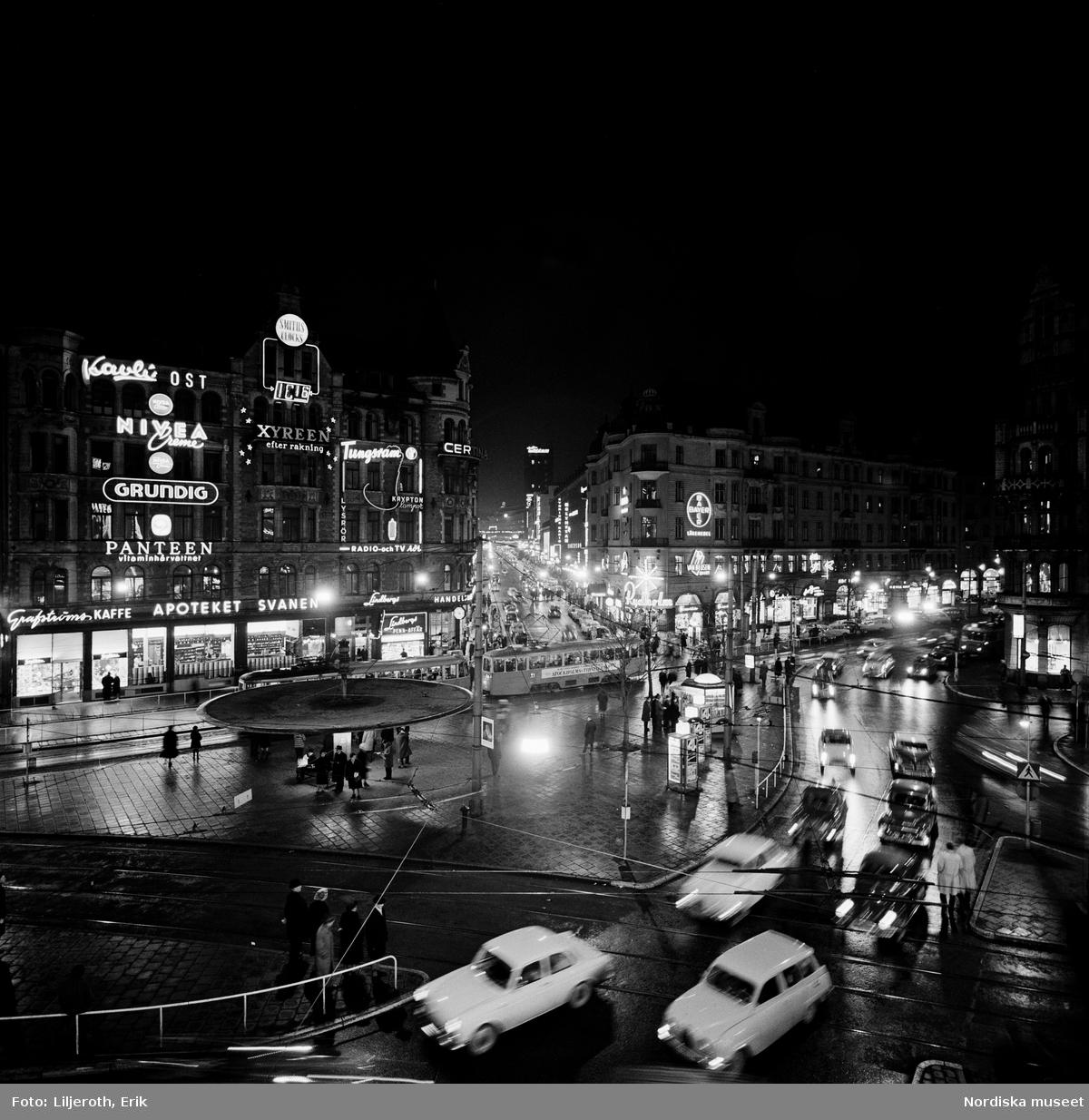 Spårvagn, bussar och bilar i trafik runt 'svampen', neonskyltar och gatubelysning tända. Stureplan, Stockholm.