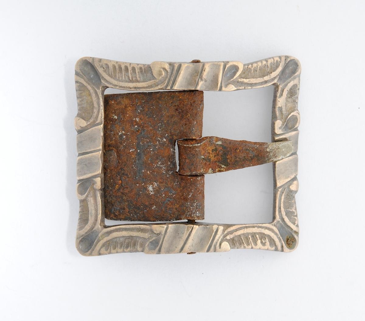 Spenne støypt i messing. Rektangulær form. Stolpe, kalv og tann i smidd jern.