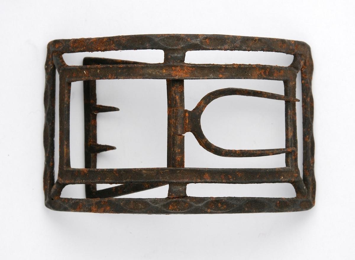 Skospenne støypt i jern. Rektangulær form, sterkt bøygd. Stolpe, kalv ( 2 piggar) og tann (2 stk.) i smidd jern. Litt rusta.
