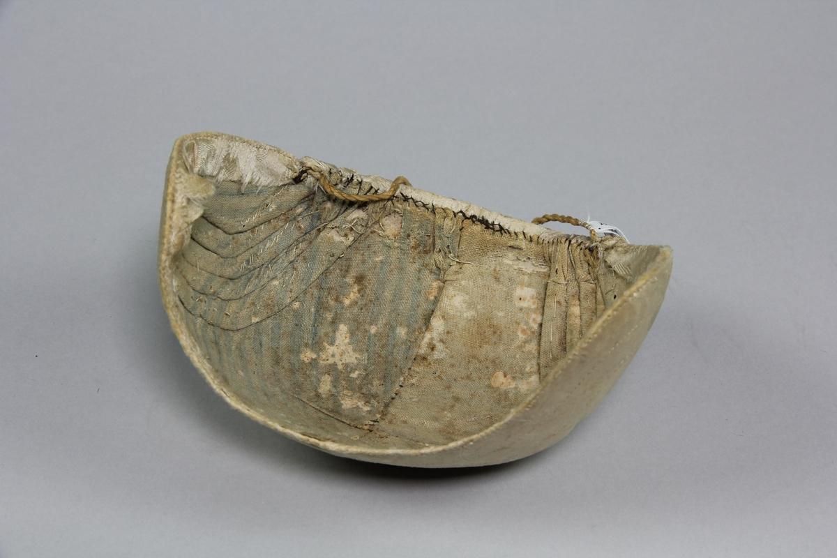 Bindmössa av benvit sidendamast och fodrad med randigt bomullstyg. Fem små veck några cm på var sidan om mittsömmen. Vecken är nersydda mot stommen och går i vinkel. Två dekorstickningar som utgår från sista vecket och går utmed hela framkanten till vecken på andra sidan. På kullen är yterligare en stickning som går mellan de innersta veckens överkant. Yttertyget är vikt om kanten och fastsytt med stygn som går genom alla tyglager och stommen. Fodettyget fastsytt med synliga stygn och limmat mot stommen. Bak finns det en snodd som kan reglera mössans storlek.