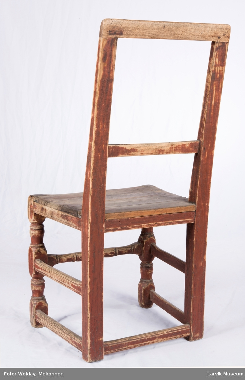 Stolen har rett toppstykke og tverrbrett. Firesidige bakstolper og bakben i ett. Svak knekk ved setet. Dreide ben foran. Sprossen foran dreiet, ellers er sprosse- verket profilert. Setet smalner mot rygg, festet med trenagler og spiker nærmest ryggen.  Høyrygget