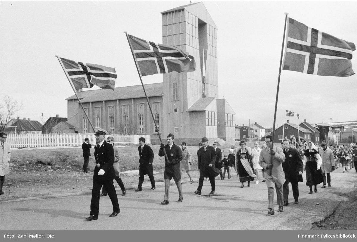 Vadsø, 17.mai 1970. Korpset spiller i gatene. Vadsø kirke i bakgrunnen.