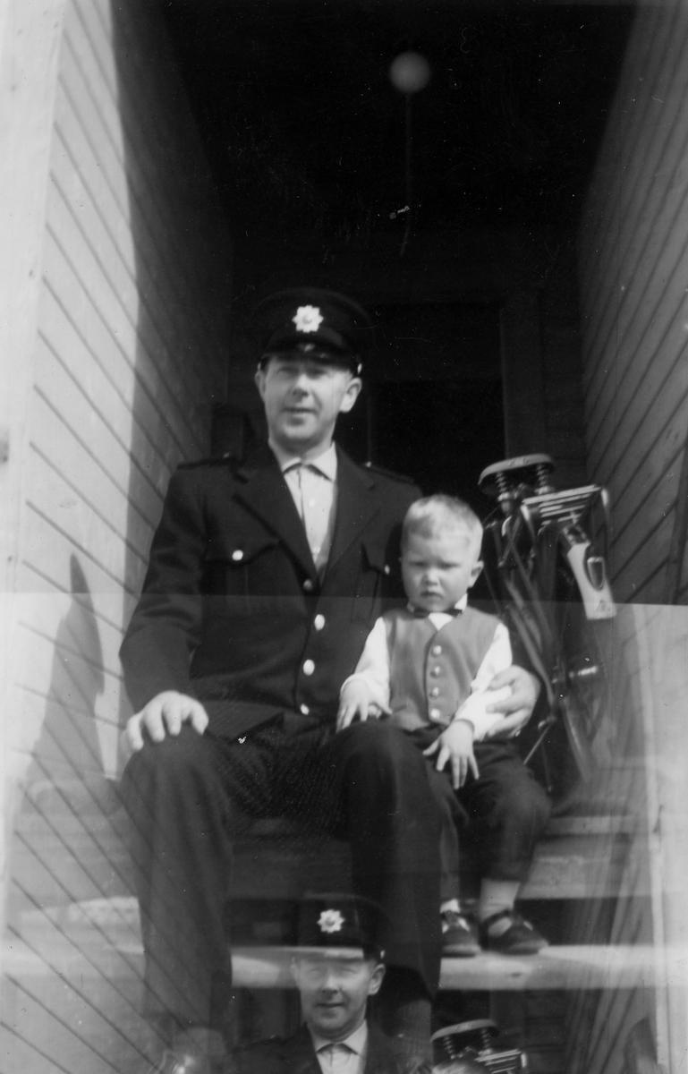 Mathis Henriksen i brannmannsunfirom med sønnen Per Johan ved sin side. Vadsø, ca. 1965.