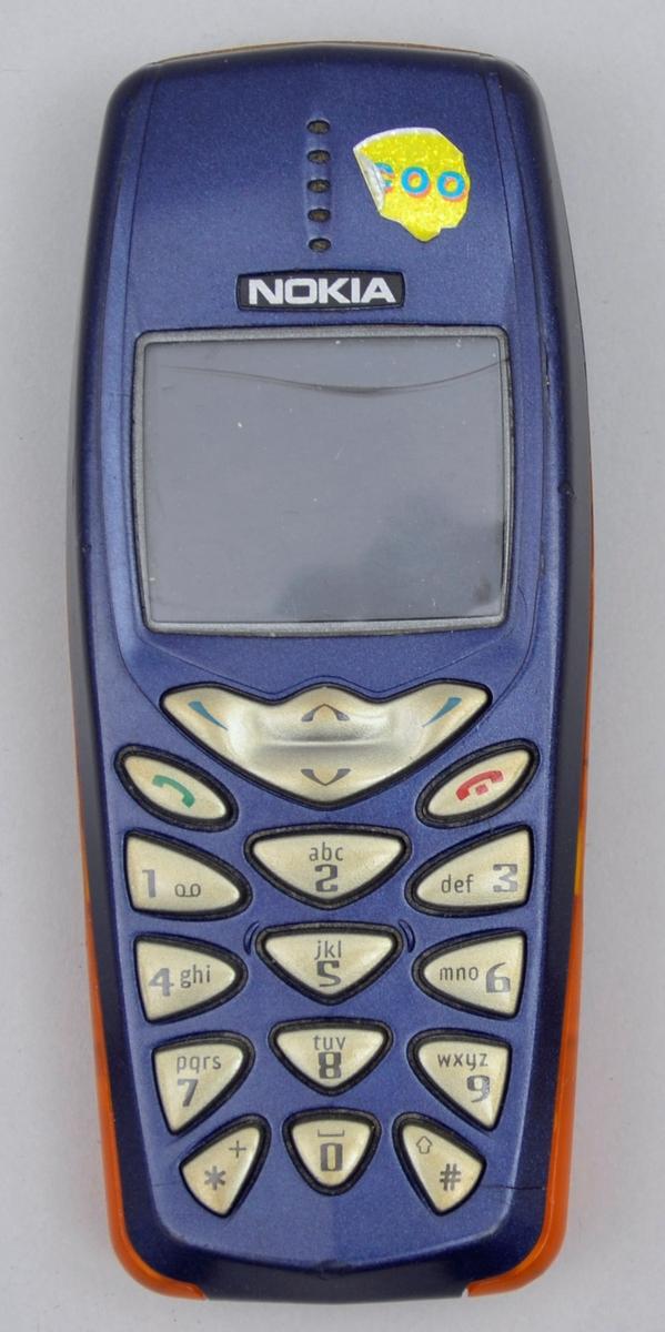 Rektangulær. Tastar og liten skjerm på eine sida. Blå med detaljar i oransj på sidane. Batteri.