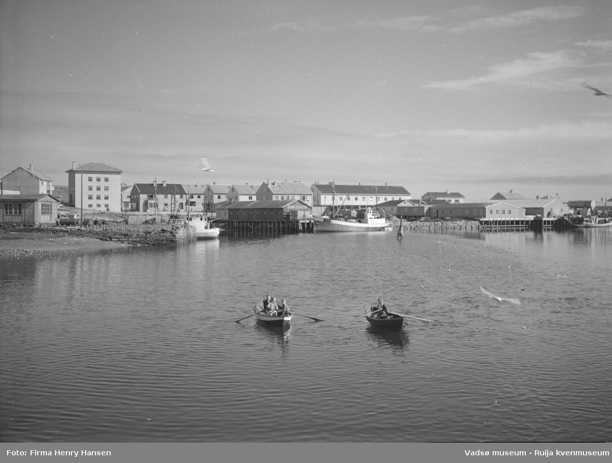Bildet er tatt mot øst og mot Vadsø sentrum. Man kan se kaiene som ble satt opp i sentrum etter krigen og det er båter som ligger ved kaia. Bildet er tatt en fin sommerdag og på bildet er det to robåter med barn eller ungdom. Mye av den nye bebyggelsen etter krigen er kommet opp.