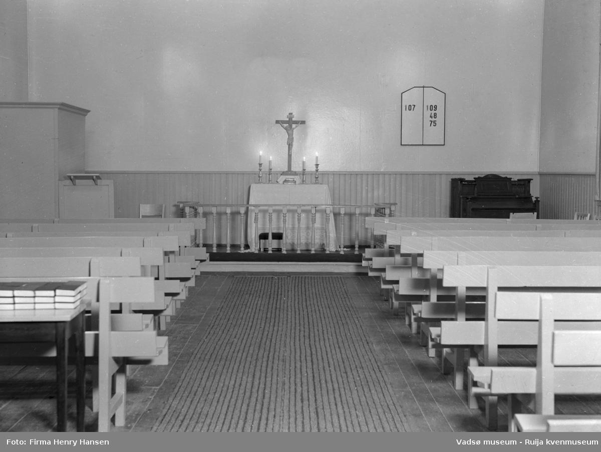 Vadsø interimkirke fotografert innvending, 1948. Fotografiet er av midtgangen med kirkebenker, alter, prekestol, orgel og salmetavle på endeveggen. Bedehuset fungerte i perioden mellom den gamle kirken brant til den nye kirken sto ferdig, som interimkirke( fra 1944 til 1958).