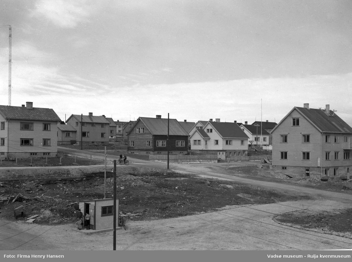 Gjenreisningsbeyggelsen i Vadsø i Midtbyen. Vi ser typiske kataloghus fra Den Norske Stats Husbank. Et næringsbygg med frisør, og en ubebygget tomt. Bildet er tatt mot nordøst.