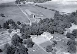Flygfoto över Ryssbylund med en bondgård och åkrar.