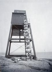 Män i badbyxor på trappa till utsiktstorn i skärgårdsmiljö