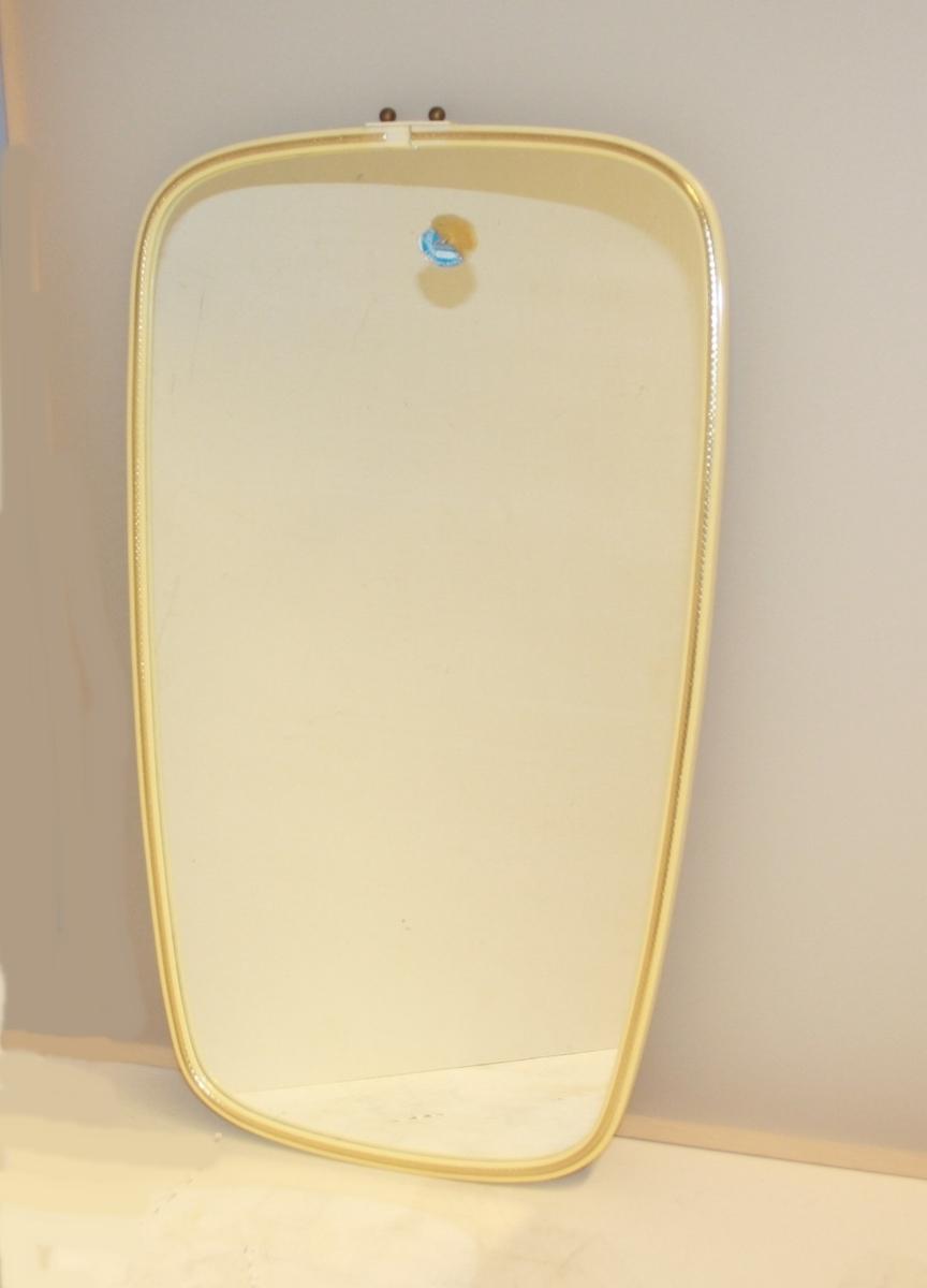 Trapesforma smal ramme med tynn gullfarga dekorkant og to små messingkuler på toppen.
