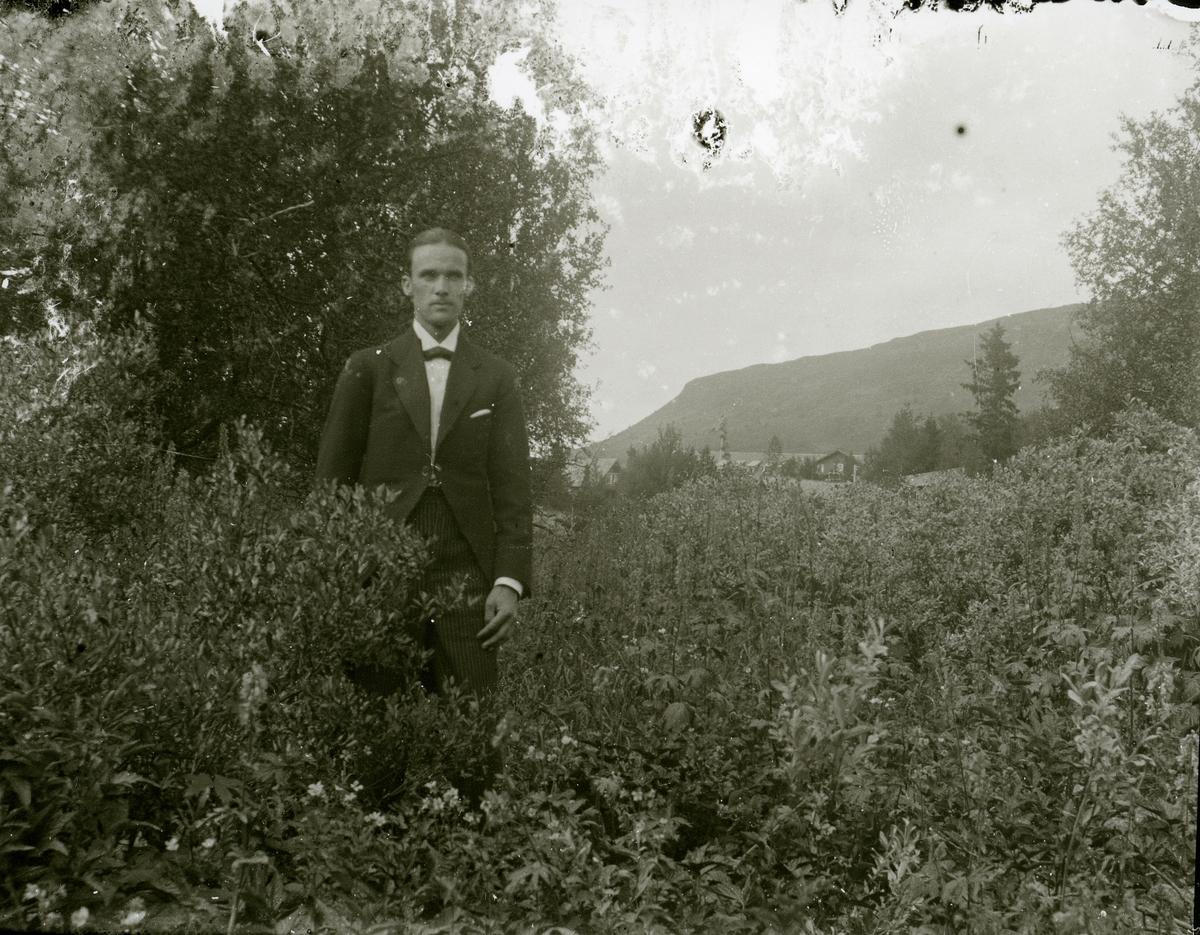 Mann ikledd dress står ute i ein hage.