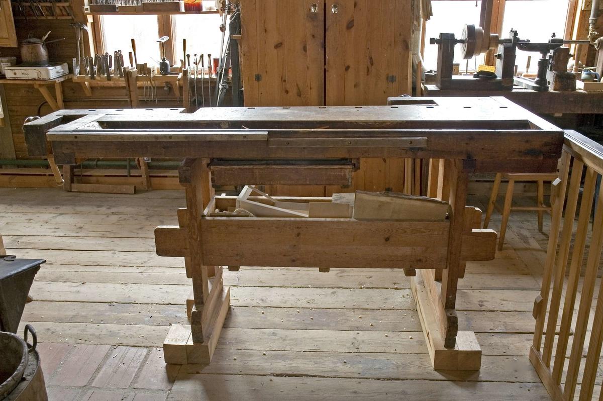 Bänk, hyvelbänk av furu för fastspänning av arbetsstycken och andra arbetsmoment. Hyvelbänken består av en tjock skiva vilande på en kraftigt byggd fotställning. Hyvelbänken har fått ökad arbetshöjd genom senare förhöjning av fotställningen med fast monterat trästycke. Förhöjningen är 80 mm. Bänken har en öppen låda och en utdragslåda märkt b. Lådmått: B=570 mm, Dj=465 mm, H=96 mm. Bänkarna har mått enligt följande: (Längd, Bredd, Höjd)   Enligt dokument i arkivet på Skansen förvärvades tre hyvelbänkar från Wirserums Nya Möbelfabrik. Dokumentationen om att dessa verkligen fördes till Skansen och i så fall vilka de är saknas.  Funktion: Arbetsyta