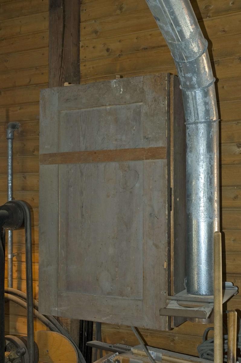Väggskåp av trä för förvaring av verktyg. Verktygsskåpet är grönmålat och dörren är tillverkad med ram och fyllning. Skåpet har elektrisk strömbrytare inbyggd. Skåpet har utdragslåda i botten märkt b.  Lådmått: B= 453 mm, Dj= 163 mm, H= 90 mm.  Funktion: Möbel för förvaring av verktyg