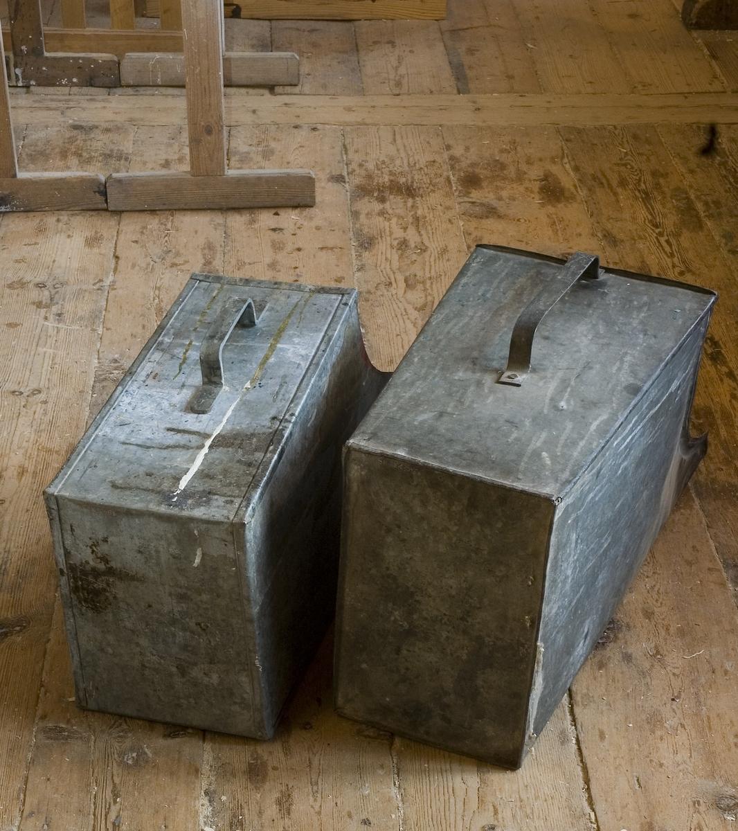 Spillåda av zinkad plåt för förvaring och bärning av spillvirke på snickeri. Låda a:s framkant är 730 mm hög och högre än bakkanten som är 480 mm. Den bakre sidan har ett fastnitat handtag som används för att bära och tippa ut spillvirke i fyren på limhällen. Kanterna på lådans sidor går ej i rät linje utan är böjda. Bredd: 300, längd 350 mm. Spillåda b är 700 mm hög i framkant och 460 mm hög i bakkanten.  Funktion: Uppsamling och transport av spillvirke