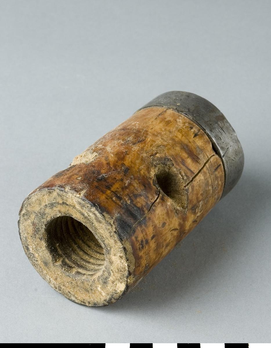 Patron av trä med en järnring. Patronen är för svarv.
