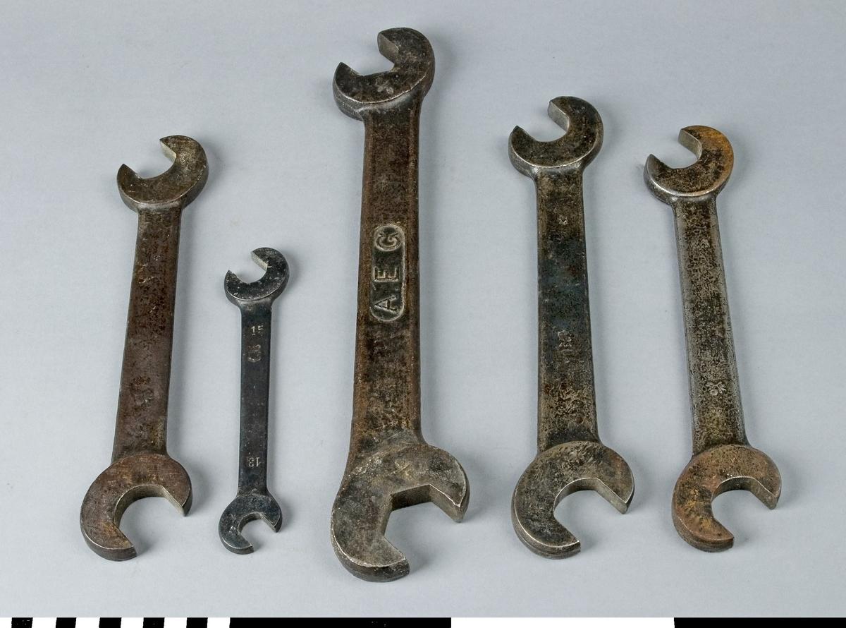 Skruvnyckel av järn, 5 st, avsedda för användning på träbearbetningsmaskinerna på Snickerifabriken. Skruvnyckeln har fast nyckelvidd och är dubbel. De olika skruvnycklarna har nyckelvidd och mått enligt följande tabell:       nyckelvidder  längd   bredd    a)     29      24       245       50         b)     15      13       170       32                                 c)     34      29       325       65                                  d)     29      24       270       55                                  e)     29      24       245       50  Skruvnyckel b har en stämpel som visar en sköld med en blomma och ovanpå skölden en krona. Skruvnyckel c är stämplad A.E.G. på ena sidan.                                     Funktion: För inställning av olika verktyg