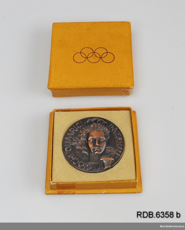 """Minnemedalje i eske fra OL i Cortina 1956. Eska er gul med OL-ringene i svart på lokket. Eska er gul innvendig, og under medaljen er skrevet """"Edvin L"""" med kulepenn. I eskelokket er skrevet """"E.L."""" med kulepenn. Medaljen er i bronsefarget metalll. På framsida et hode samt OL-ilden i relieff og påskrift. På baksiden en stor snøkrystall og påskrift i relieff."""