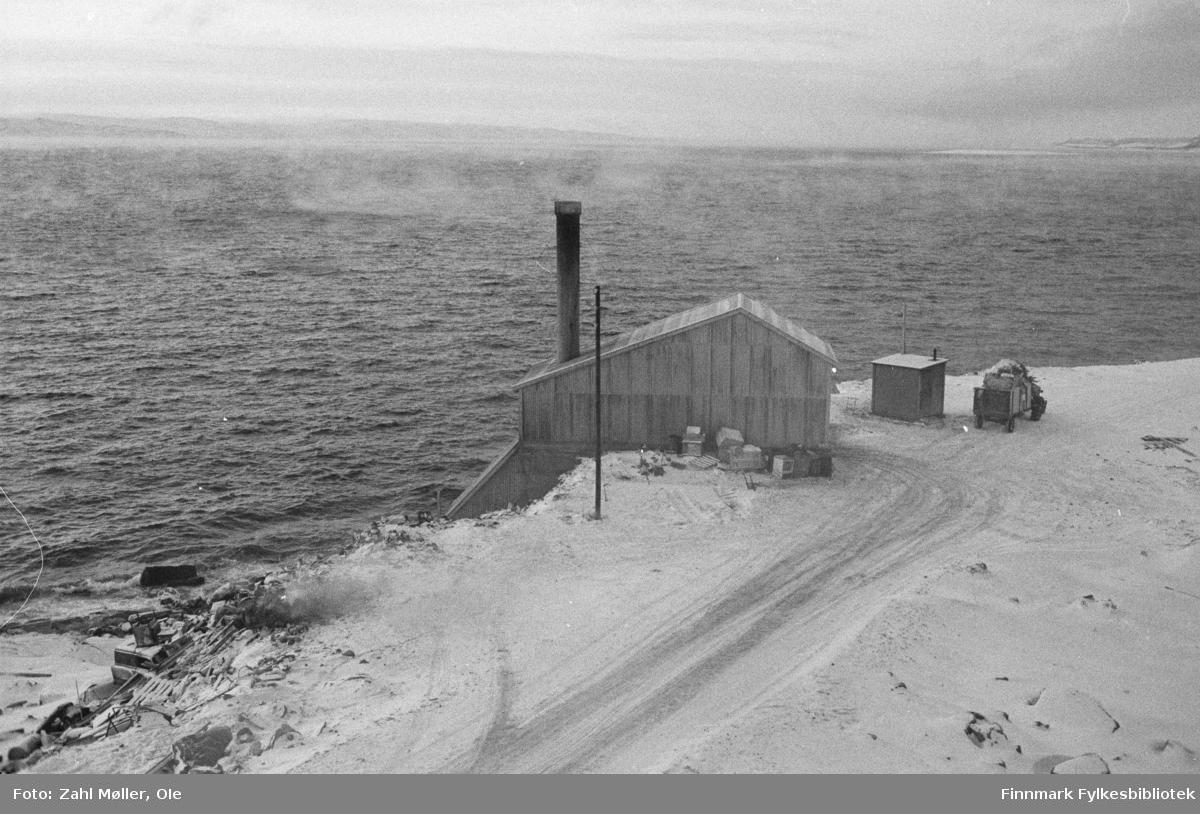 Vadsø 1968-69. Dette vinterbildet er tatt ute på Vadsøya i 1968. Bildet viser området ved  Vadsø sildoljefabrikk som ble etablert i 1953 og hadde sitt siste produksjonsår i 2009. Sildoljefabrikken var frem til slutten av 1900-tallet den desidert største industriplassen i Vadsø.
