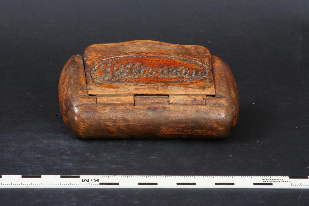 Snusdosa av björkträ, invändigt näverklädd.  Lock med gångjärn. På locket skuren dekor i form av oval, prickig lockspegel med namn.  Har rester av brun färg på locket.