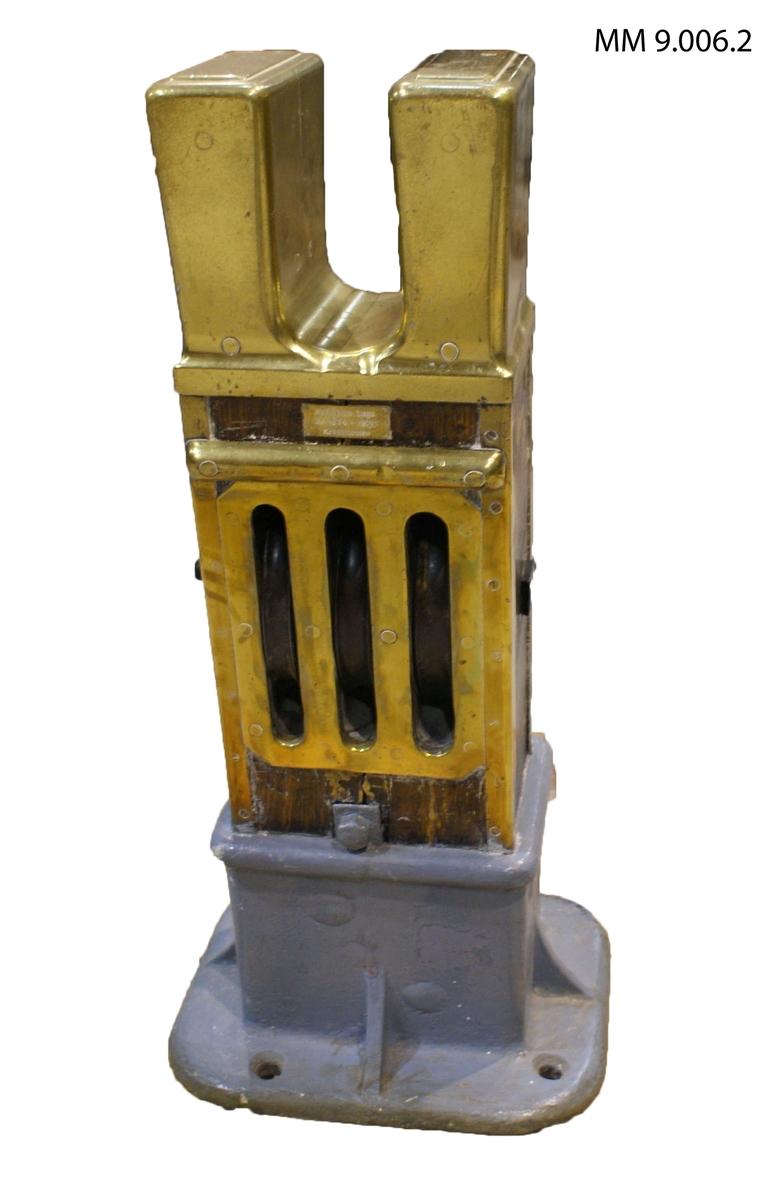 Knekt från korvetten Saga. Rektangulär form. Fastsatt i lampa av gjutjärn. På mitten tre blockskivor av gjutjärn för löpande tågvirke. Överkanten utformad till två pollare för fastgöring av tågvirket. Lampan försedd med fyra bulthål för fastsättning i däck. Märkta på mässingsbricka: Korvetten Saga År 1874 - 1928 Kryssmasten.