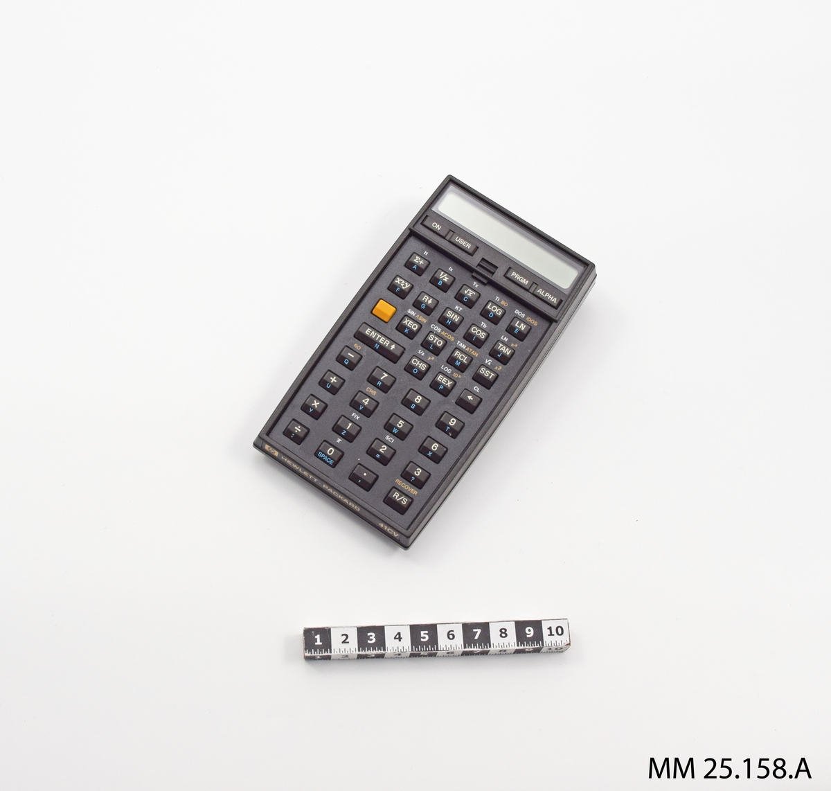 """Miniräknare i svart plasthölje. Högst upp finns en avlång display med plats för en text i en rad. Därunder en rad med fyra tangenter märkta: """"ON"""", """"USER"""", """"PRGM"""" och """"ALPHA"""". Under den översta knappraden finns en nedsänkning i plasten och däri sitter alla radiakräknedosans funktionstangenter. I de övre raderna tangenter för att välja matematiska funktioner som sinus, cosinus och så vidare. Nedre halvan har siffertangenter. På den nedre kortsidan text tryckt på plasten: """"hp HEWLETT PACKARD 41CV"""". Övre kortsidan märkt """"RADIAK"""". På baksidan av radiakräknedosan finns tryckt i brandgult en översättningsnyckel för vilka bokstäver varje knapp motsvara om operatören vill skriva in text. Däröver finns ett klistermärke som anger radiakräknedosans föråddsbeteckning och förrådsbenämning. I relief i övre högra hörnet finns text: """"SERIAL NO. 2906S20896""""."""