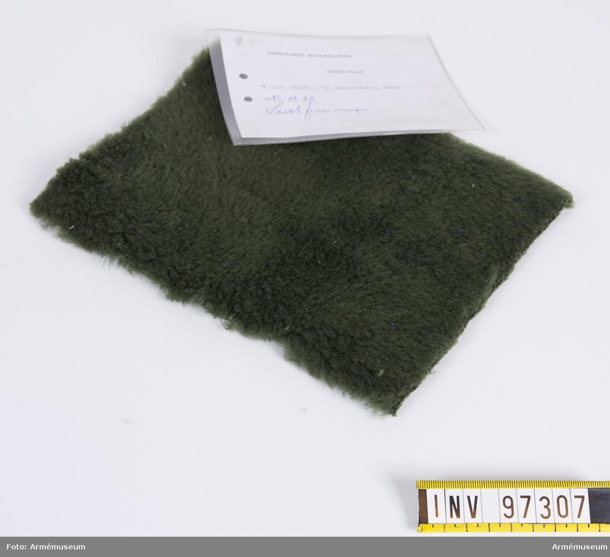 """Vidhängande modellapp med text: """"Försvarets materielverk. Fastställs. M 1016-682000-6. Polyamidpäls, Foder 1985-08-20 (oläslig sign)"""""""