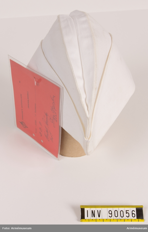"""Vit kockmössa av bomull. Invändigt märkt """"Tre kronor 1978, Trivab"""" samt etikett med storlek 56. Vidhängande modellapp med text: """"Försvarets materielverk. Fastställs. M 7370-705000-4 Kockmössa 1985-09-18. (oläslig underskrift)."""""""