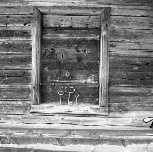Utsidan av en dörr med ett flertal nyckelhål och tillhörande nycklar som står uppradade på dörrtröskeln nedanför. Dörren fotograferades i Fågelsjö 20-21 oktober 1982.