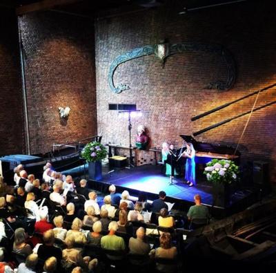 Musikkfestivalen Kon-Tiki-festivalen i Sentralhallen på museet. Publikum i forgrunnen, utøvere bak: Ei spiller fiolin, ei spiller piano.