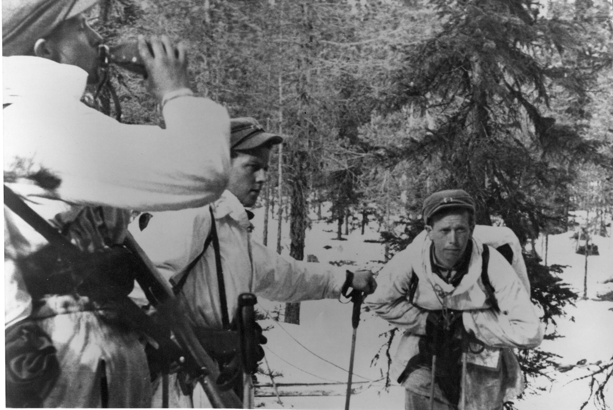 Vinterövning, soldater rastar i snöklädd skog.